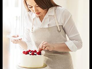 a women in a process of decorating a cute cake