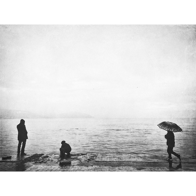 #blackandwhite #rain #sea #minimal #umbrella #people #mobilephotography #rainyday