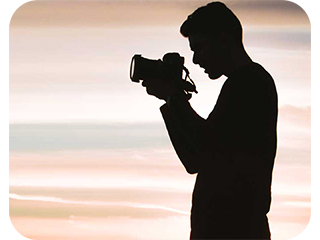 a man silhouette holding a photo camera
